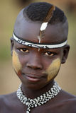 Young Mursi boy at a ceremony in South Omo, Ethiopia. Young Mursi boy with feather and face painting at a ceremony in South Omo, Ethiopia Royalty Free Stock Photo