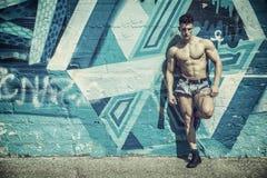Young muscle man leaning on graffiti wall. Attractive young shirtless muscle man leaning on colorful graffiti wall, wearing only denim shorts Stock Photo