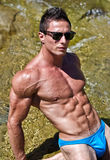 Young muscle man outdoors in water showing muscular abs, pecs and arms Stock Images