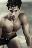 Young muscled italian man at the beach shirtless. Sexy pose Royalty Free Stock Photo