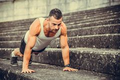Doing a push up outdoor. Young, muscular athlete is doing a push up outdoor Stock Image