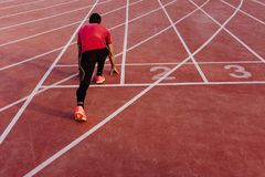Young muscular athlete is at the start of the race tracks line at the stadium. Sports concept.  stock photo