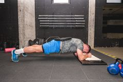 Young muscular attractive and active man workout plank exercise in the gym for strength and conditioning with barbell weight plate royalty free stock images