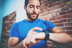 Young Muscular bearded athlete checking burned calories on electronic smart watch application after good indoor workout Royalty Free Stock Photo