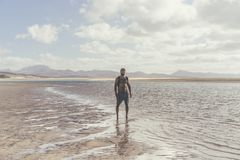Young muscular bearded man standing on the sea shore at sunrise. Side portrait of healthy young bearded man running at. The beach with bright sunlight Stock Photo