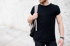 Young muscular bearded man wearing black tshirt and backpack posing outside. Empty white concrete wall on the background stock photos