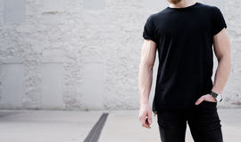 Young muscular bearded man wearing black tshirt and jeans posing outside. White bricks wall on the background Stock Photo