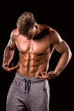 Young muscular bodybuilder boy showing his abdominal muscle. On black background royalty free stock photography