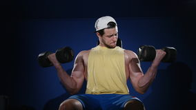 Young muscular built athlete working out in a gym, sitting on a weightlifting machine and lifting two dumbbells.  stock footage