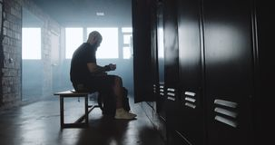 Young muscular Caucasian man putting backpack inside locker in dark gym changing room before workout slow motion. Sportswear and equipment, male athlete before stock footage