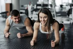Young muscular couple doing doing hard workout at the gym. Doing plank in the gym.  royalty free stock images