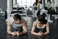 Young muscular couple doing doing hard workout at the gym. Doing plank in the gym.  stock image