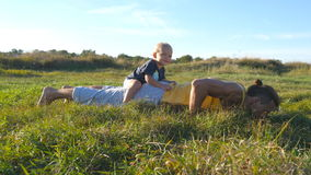 Young muscular father doing push ups with his little son on his back. Athletic man doing push-ups at green grass with stock video