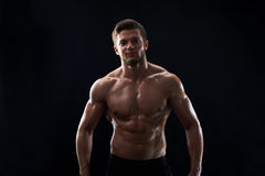 Young muscular fit sportsman posing shirtless on black backgroun. Handsome young shirtless athletic man smiling to the camera posing confidently on black Royalty Free Stock Images