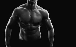 Young muscular fit sportsman posing shirtless on black backgroun. Horizontal cropped black and white studio shot of a muscular sexy torso of an athletic man Royalty Free Stock Photo