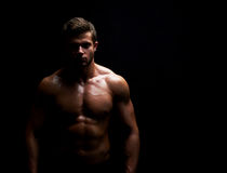 Young muscular fit sportsman posing shirtless on black backgroun. Horizontal studio shot of a young shirtless athletic man with sexy hot muscular ripped body Royalty Free Stock Photo