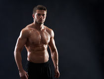 Young muscular fit sportsman posing shirtless on black backgroun. Young strong athletic handsome man posing on black background copyspace shirtless male Royalty Free Stock Photography