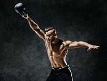 Young muscular guy training with kettlebell. Photo of handsome man with naked torso on dark background. Strength and motivation stock photography