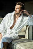 Young, muscular, handsome, healthy male relaxing on a couch in a. Young, muscular, handsome, healthy male in a robe relaxing on a couch in a hotel and looking royalty free stock photos