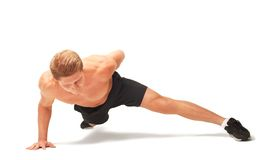 Young muscular handsome shirtless sportsman doing push-ups on one arm. Isolated on white background Stock Photos