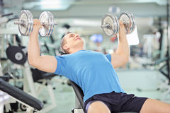 Young muscular male lifting weights in a gym. Young muscular man lifting weights in a gym Stock Photography