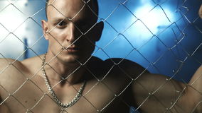 Young muscular man beyond wire in jail. Sad bald topless man looking at camera while standing beyond wire fence in prison then looking down