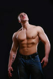 Young and muscular man on black Stock Photos
