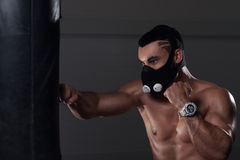 Young muscular man boxing in high altitude mask. Portrait of young muscular man exercising in high altitude mask, doing boxing workout. sports, fitness concept royalty free stock photos
