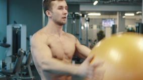 Young Muscular Man Doing Lunges Holding Gym Ball stock footage