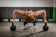 Push-Up. Young muscular man doing push-up exercise with dumbbell. Strong male doing crossfit workout royalty free stock photo