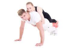 Young muscular man doing push ups with beautiful woman on back i. Young muscular men doing push ups with beautiful women on back isolated on white background stock photography