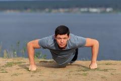 Young muscular man doing push-ups outdoors. Stock Photo