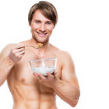 Young  muscular man eating flakes. Royalty Free Stock Photography