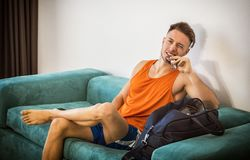 Man eating protein bar at home on sofa. Young muscular man eating protein bar indoor at home sitting on a couch royalty free stock image