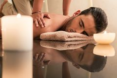 Young man enjoying the healing benefits of traditional Thai massage. Young muscular man enjoying the healing benefits of traditional Thai massage at luxury spa Stock Photo