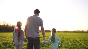 Young, muscular man, father is holding his small daughters with hands. Walking by the wide meadow. Casual clothes. Sun. Rays. Footage from the backside stock video footage