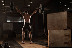 Young muscular man lifting barbell over head Stock Images