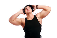 Young muscular man listen music. Isolated over white background Royalty Free Stock Photos