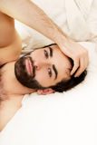 Young muscular man lying in bed. Royalty Free Stock Images