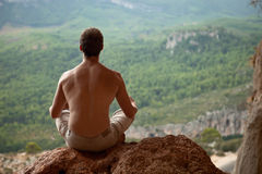 Young muscular man meditating on rock Royalty Free Stock Image