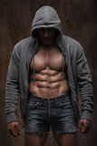 Young muscular man with open jacket revealing muscular chest and abs.  Stock Photo