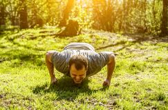 Young muscular man with painful face expression doing hard difficult last push-ups approach. Young muscular man with painful face expression doing hard difficult stock photography