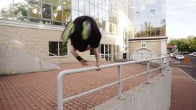 Young muscular man is performing a stunt by jumping over the railing of a staircase. Stuntman, parkour, freerun concepts. Modern building on the background stock video footage