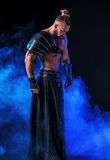 Young and muscular man performing a theatrical pose on  stage. Stock Images