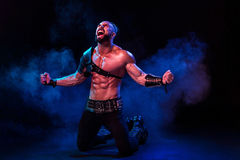 Young and muscular man performing a theatrical pose on  stage. Royalty Free Stock Photo