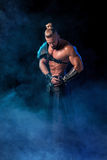 Young and muscular man performing a theatrical pose on  stage. Royalty Free Stock Photography