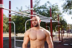 Young muscular man posing on a city sports field. stock images