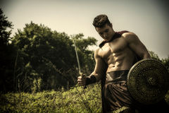 Young muscular man posing in gladiator costume Stock Images