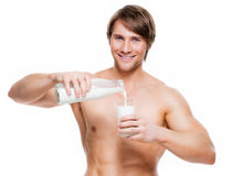 Young  muscular man pouring milk into a glass . Portrait of a young handsome muscular man pouring milk into a glass - isolated on white background Royalty Free Stock Photography