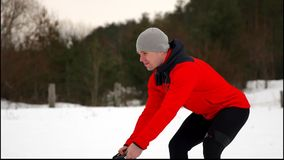 Young muscular man in red jacket training with battle ropes winter and snow Slow motion. Fitness workout outdoors. Young muscular man in red jacket training stock footage